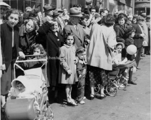 View of a crowd of people watching the Manchester NH Centennial Parade (1946) at the corner of Spruce and Elm Streets.  Eric M. Sanford photographer. Manchester Historic Association Photo Collection. Used with Permission.