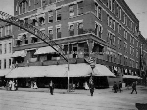 1912 view of Pembroke Block, James W. Hill and Company, north east corner of Elm and Merrimack Streets. On the second floor is the National Life Insurance Company, On Merrimack Street a sign for the Manchester House is seen, across Elm Street a electric arch visible. American flags and bunting hang from the building and people are seen crossing the street or on the sidewalk. From Manchester Historic Association Collection. Used with permission.