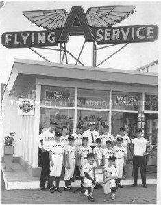 "Group photograph of Hickman's Little League team at Hickman's Service Station, with ""Flying A Service"" sign at 16 Milford Street, Manchester. Photo identified as ""1961 South West Little League Champions - Wolf's Little League Park."" 1st Row (holding plaque): Short Stop Bob Michaud, Secord Baseman Mike McDonald. 2nd Row: Outfielder Jim Alger, Outfielder Norm Bellemore, Infielder Bob Eldridge, Pitcher Bob Christo, Infielder Don Huot, Catacher Bill Prive; 3rd Row: Coach Don Anderson, Centerfielder Tom Caldwell, Pitcher Ron Boulanger, Sponsor Hap Hickman, Utility Man Jean Biron, Rightfielder Jim Norton, Manager Ed ""Casey"" Forbush. Absent when photo was takere were Thirdbaseman Tim Mullen and Left Fielder Scott Keller. (Eric M. Sanford photographer). From the Manchester Historic Association Collection, used with their permission."