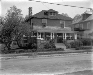 View of Reverend A. S. Yantis House, 266 Harrison Street, a two story hipped roof with dormer, a stone chimney, and a front column porch. A man sits on the front porch to the right of the front door. Arnold S. Yantis served as pastor of the Universalist Church c. 1920. Manchester Glass Plate Negative Collection, MHS.