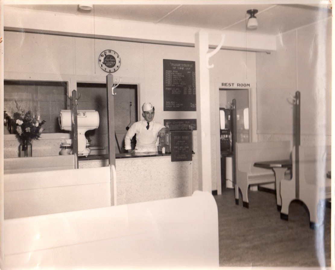 Saul Gordon proprietor of Gordon's Fried Sea Foods standing at the counter in his shop circa 193?