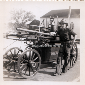 Photograph of a man with the Tiger No. 1 hand-tube fire engine of Newmarket, NH.