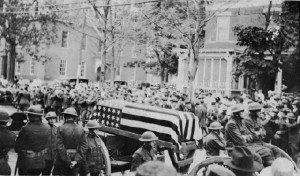 View of William H. Jutras flag draped casket, St. Raphael's Parish. The casket is on a caisson with soldiers on both sides of the street. MHA Photoprint Collection, Manchester Historical Association.